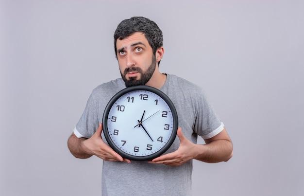 Réfléchi jeune bel homme tenant horloge et levant isolé sur mur blanc