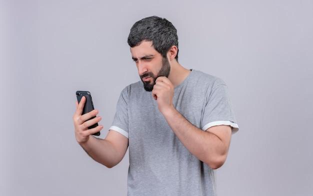 Réfléchi jeune bel homme tenant et regardant le téléphone mobile et toucher son menton isolé sur un mur blanc