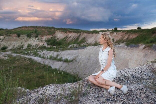 Réfléchi jeune femme assise au fond du paysage naturel