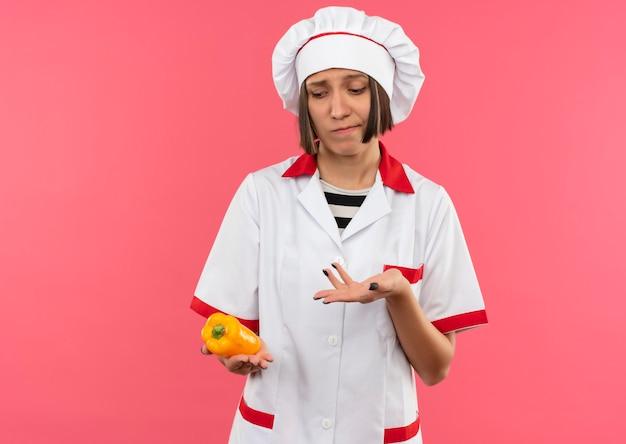 Réfléchi jeune femme cuisinier en uniforme de chef tenant à la recherche et pointant avec la main au poivre isolé sur mur rose