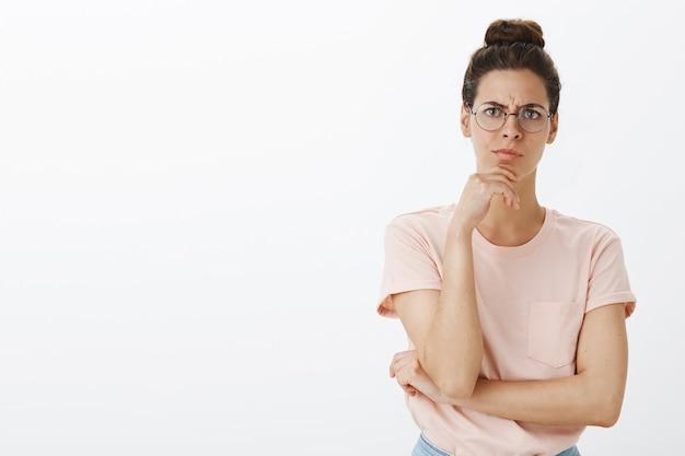 Réfléchi jeune femme élégante posant contre le mur blanc
