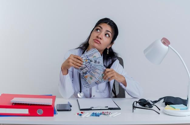 Réfléchi jeune femme médecin portant une robe médicale et un stéthoscope assis au bureau avec des outils médicaux tenant de l'argent à côté isolé