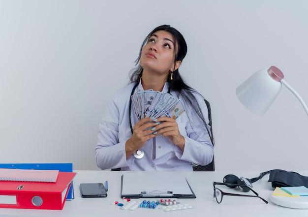 Réfléchi jeune femme médecin portant une robe médicale et un stéthoscope assis au bureau avec des outils médicaux tenant de l'argent en levant isolé