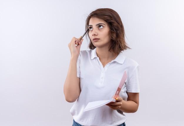 Réfléchi jeune fille aux cheveux courts portant un polo blanc tenant un cahier et un stylo à côté avec une expression pensive