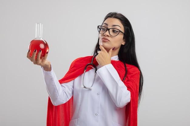 Réfléchi jeune fille de super-héros caucasien portant des lunettes et un stéthoscope tenant et regardant flacon de produit chimique avec un liquide rouge touchant le menton isolé sur fond blanc avec espace de copie