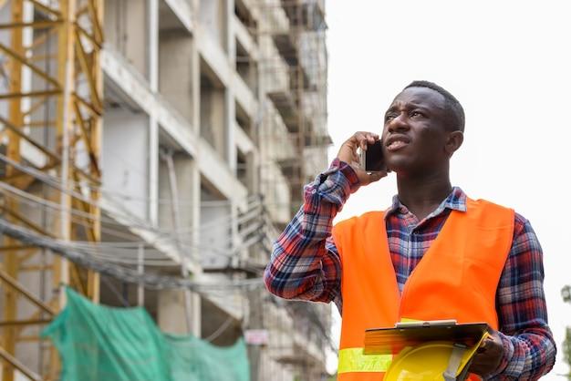 Réfléchi jeune homme africain noir travailleur de la construction parler au téléphone