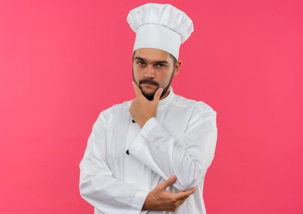 Réfléchi jeune homme cuisinier en uniforme de chef mettant la main sur le menton et le coude isolé sur l'espace rose