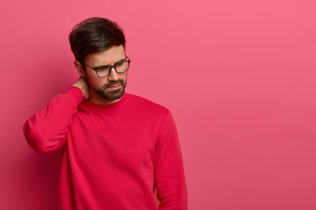 Réfléchi jeune homme gênant en lunettes concentré vers le bas