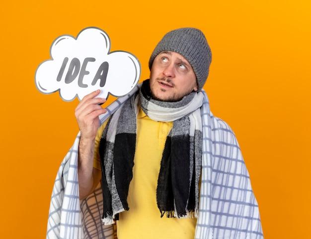 Réfléchi jeune homme slave malade blonde portant un chapeau d'hiver et une écharpe enveloppée dans un plaid détient bulle d'idée en levant isolé sur un mur orange avec espace de copie