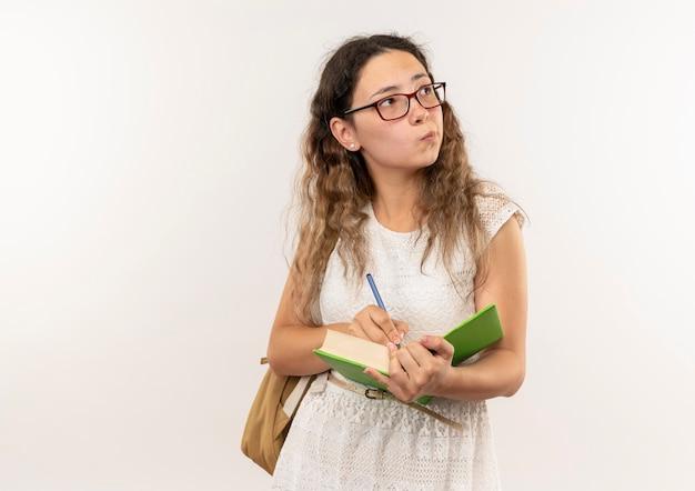 Réfléchi jeune jolie écolière portant des lunettes et sac à dos écrit sur livre avec stylo à côté isolé sur mur blanc