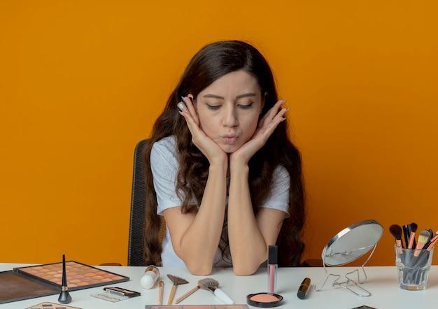 Réfléchi jeune jolie fille assise à la table de maquillage avec des outils de maquillage mettant les mains sous le menton et en regardant les outils de maquillage isolés sur fond orange
