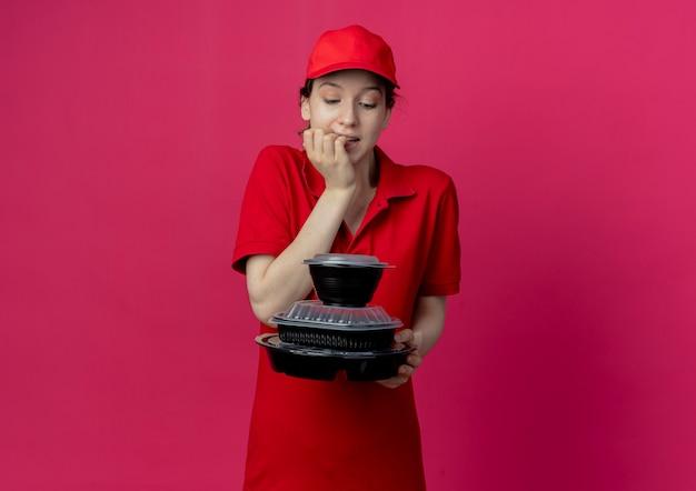 Réfléchi jeune jolie livreuse portant un uniforme rouge et une casquette tenant et regardant des contenants de nourriture et des doigts mordants isolés sur fond cramoisi avec espace de copie