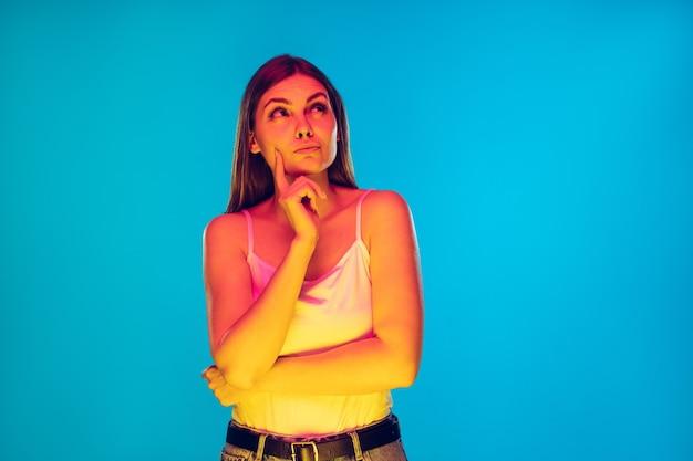 Réfléchi. portrait de jeune femme caucasienne isolé sur fond bleu à la lumière du néon. beau modèle féminin en tenue décontractée. concept d'émotions humaines, d'expression faciale, de ventes, d'annonces. espace de copie.