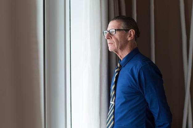 Réfléchi senior businessman looking out window