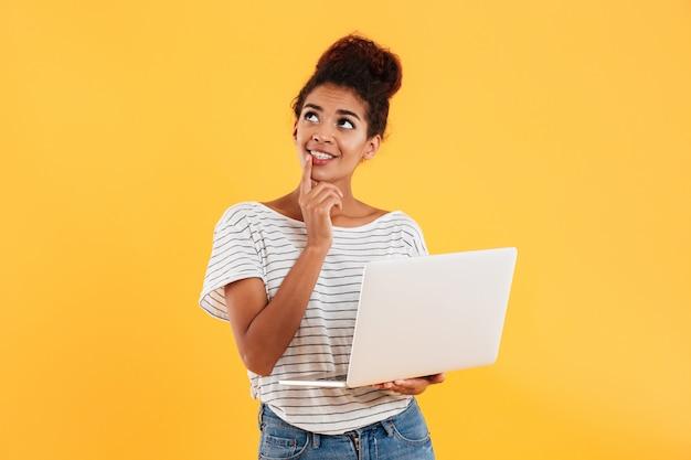 Réfléchie dame souriante levant et tenant un ordinateur portable isolé
