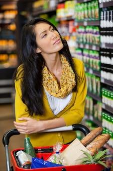 Réfléchie femme debout avec panier dans la section épicerie