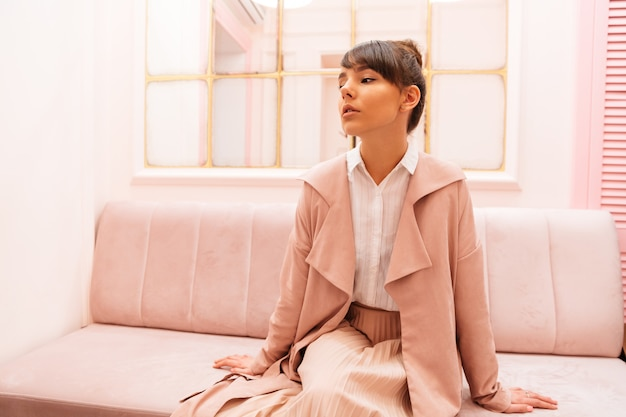Réfléchie femme en manteau assis sur un canapé au café
