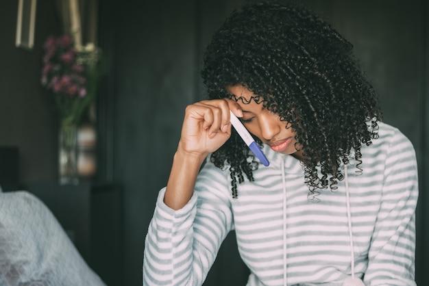 Réfléchie femme noire inquiète et triste avec test de grossesse au lit