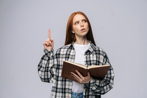 Réfléchie jeune femme étudiante tenant un livre et pointant le doigt vers le haut en regardant la caméra