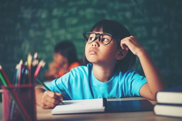 Réfléchie petite fille avec un livre près d'une commission scolaire