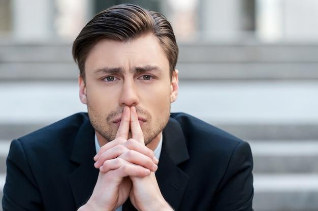 Réfléchir aux solutions. portrait de jeune homme en tenue de soirée tenant les mains jointes et regardant loin alors qu'il était assis à l'extérieur