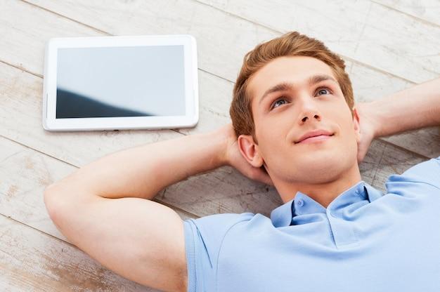 Réfléchir aux solutions. vue de dessus du beau jeune homme allongé sur le sol dans son appartement tandis que la tablette numérique se trouve près de lui