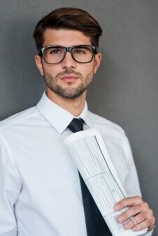 Réfléchir à de nouvelles solutions. jeune homme confiant en chemise et cravate tenant le journal