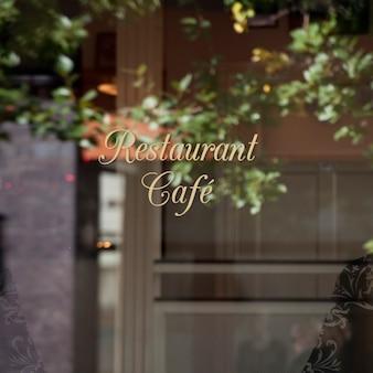 Reflet de l'arbre et de l'immeuble de bureaux dans une fenêtre de signalisation du restaurant