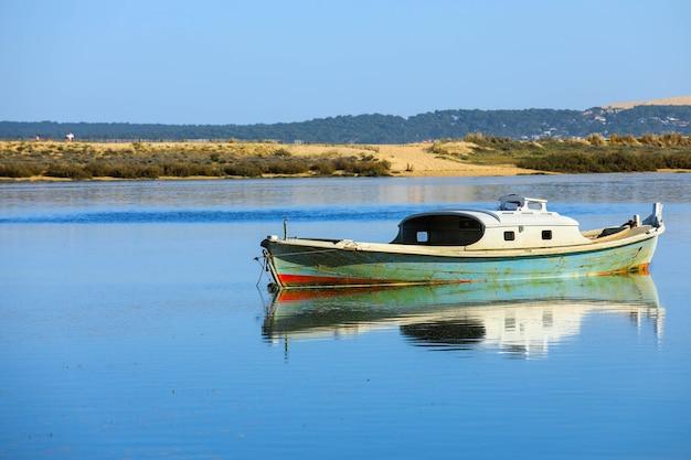 Reflet de bateau sur la baie du bassin d'arcachon et vue sur la pointe du cap-ferret, bordeaux, gironde, france