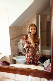 Reflet dans le miroir d'une petite fille appliquant de la poudre