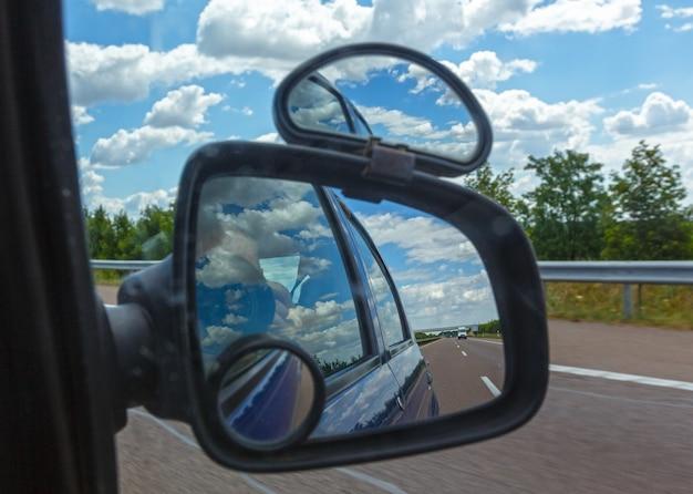 Reflet du ciel avec des nuages dans le miroir latéral d'une voiture.