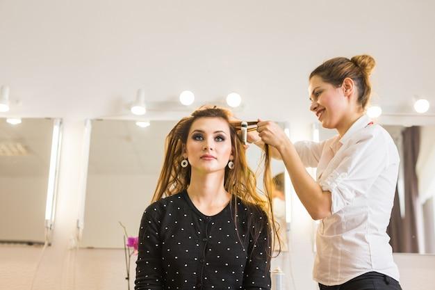 Reflet du coiffeur faisant la coiffure pour femme chez le coiffeur. concept de mode et de beauté
