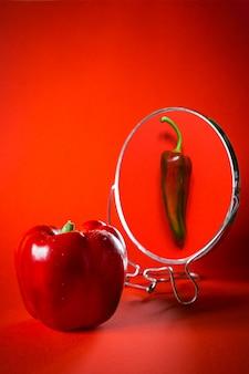 Le reflet d'épais poivron rouge dans le miroir est l'inverse.