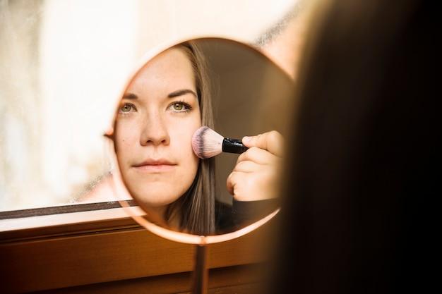 Reflet d'une femme appliquant un fard à joues sur son visage