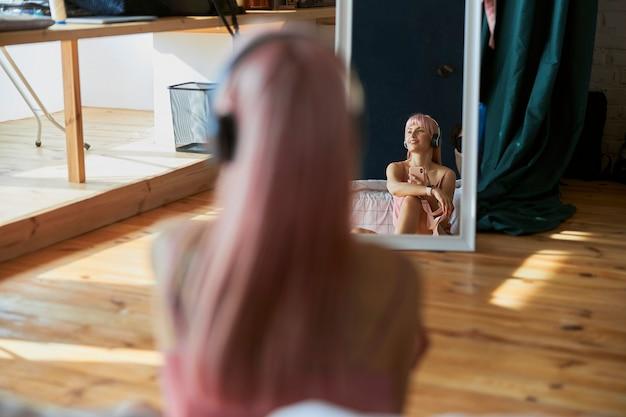 Reflet d'une femme réfléchie aux cheveux de couleur écoutant de la musique devant un miroir