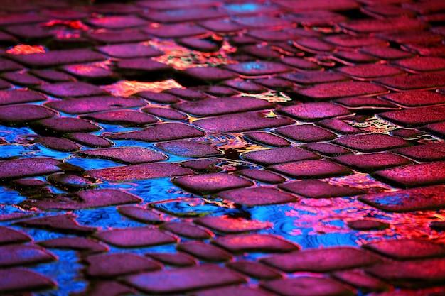 Reflet des lumières publicitaires sur les pierres de la route sous la pluie