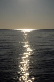 Reflet lumineux de la lune jusqu'à l'horizon sur les vagues calmes de la mer en fin de soirée