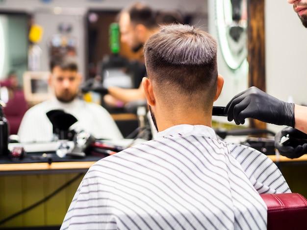 Reflet miroir flou du client dans le salon de coiffure
