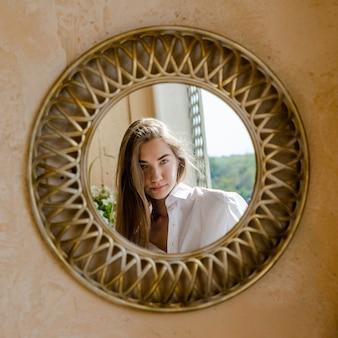 Reflet miroir gros plan du visage d'une femme. réflexion dans un miroir rond, femme aux cheveux blonds.