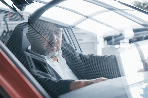 Reflet de la pièce dans la vitre avant de la voiture. homme d'affaires senior à l'intérieur