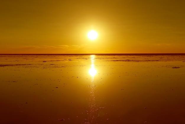 Reflet d'un soleil éclatant sur les marais salants d'inondation l'effet miroir emblématique au salar de uyuni bolivie