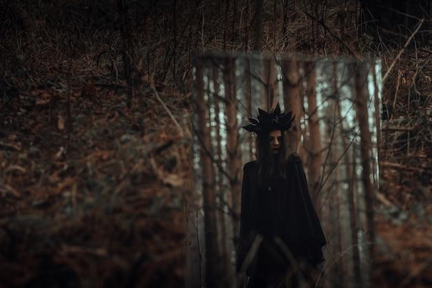 Reflet d'une sombre sorcière effrayante dans un miroir dans une forêt sombre