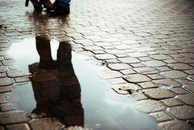 Reflété dans une route de plein air couple flaque d'eau