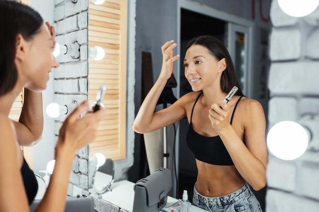 Réflexion de la belle jeune femme appliquant son maquillage, regardant dans un miroir