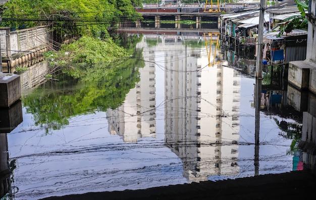 Réflexion de la construction sur la rivière et la communauté d'accueil riveraine