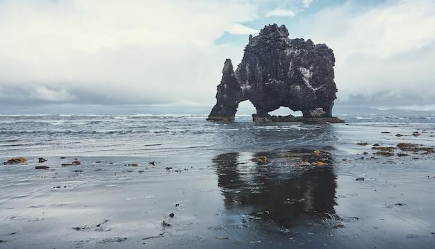 Réflexion dans le sable noir du ciel et un gros rocher avec des arches sur la côte. roche de hvítserkur