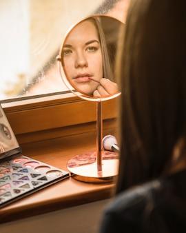 Réflexion du visage d'un mannequin appliquant du rouge à lèvres sur ses lèvres