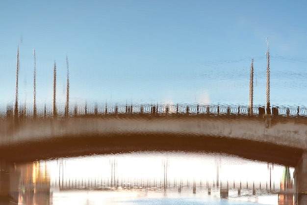 Réflexion floue d'un pont sur la surface d'une rivière urbaine polluée.