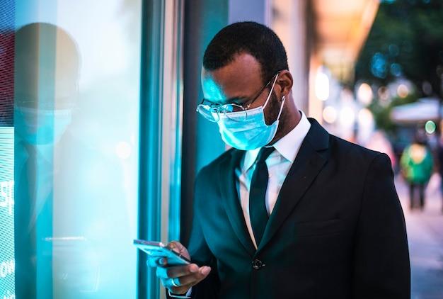 Réflexion hors de la ville d'un homme d'affaires noir avec un masque de protection. lumières bleues à led ou néon le soir.
