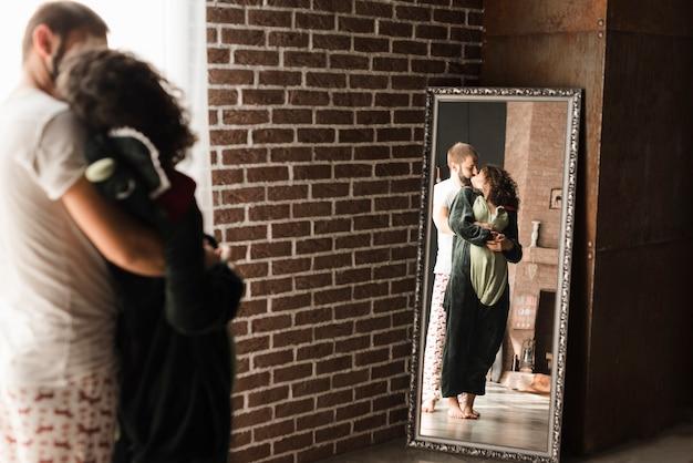 Réflexion de jeune couple s'embrassant dans le long miroir rectangulaire